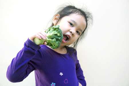 Little girl eating broccoli - healthy food photo