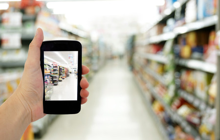 web store: hand hold smartphone in supermarket Stock Photo
