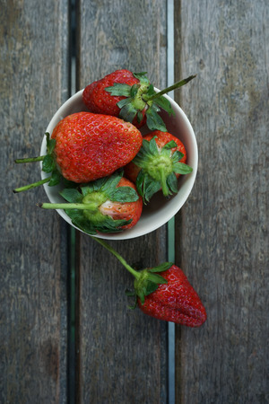 fresh ripe red strawberries in bowl on wooden textured table to photo