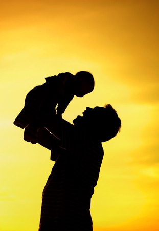 father holding and raising his son silhouette photo