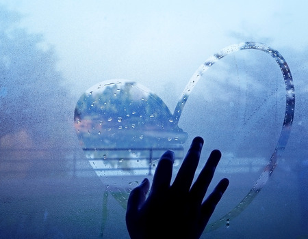hand drawing heart on wet window Archivio Fotografico
