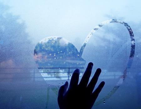 hand drawing heart on wet window Standard-Bild