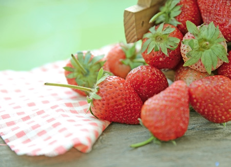 Spring fruits, strawberries in wooden bucket on a vintage wooden table photo