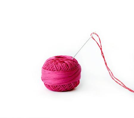 hilo rojo: Bola de hilo rojo y aguja con hilo rojo aislado en blanco Foto de archivo