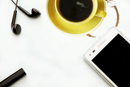 스마트 폰 이어폰과 사무실 책상에 커피 한 잔