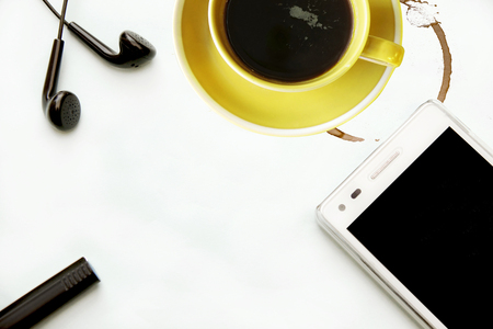smart phone earphones and a cup of coffee on an office desk Stockfoto