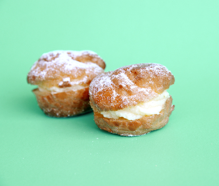 profiterole: Profiterole or cream puff with filling and powdered sugar topping