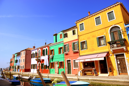 Venice landmark, Burano island canal, colorful houses and boats, Italy photo