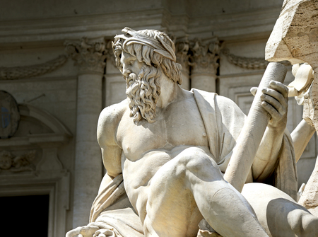 famous statues: Statue of the god Zeus in Berninis Fountain of the Four Rivers in the Piazza Navona, Rome Stock Photo