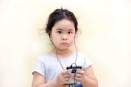 Little girl listen music with a MP3 player Stock Photo