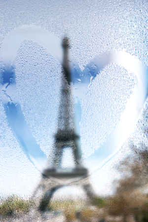 traditionally french: France, Paris, Eiffel Tower in a rainy day with draw heart on wet glass