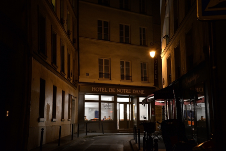 april 15: FRANCE, PARIS - APRIL 15, 2015: night street scene in traditional Parisian hotel near famous Notre Dame de Paris on April 15, 2015 in Paris, France