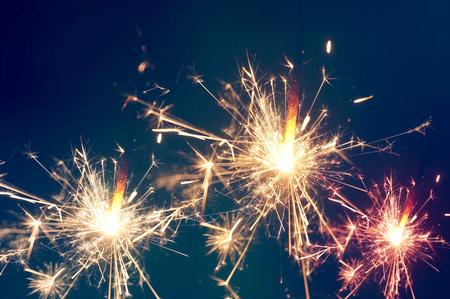 sparklet: Burning christmas sparkler on blue background