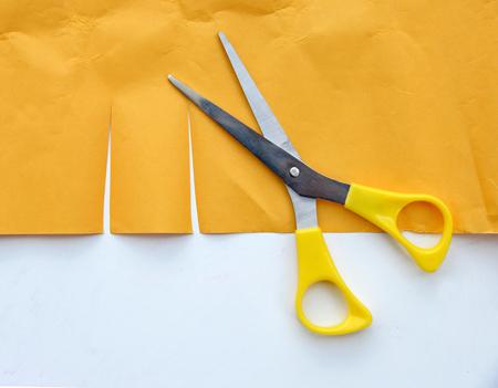 haircutter: scissors cutting yellow paper