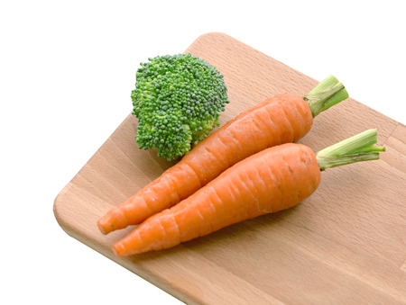 brocoli: Fresh carrots and brocoli on wooden plate Stock Photo