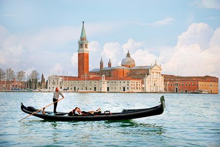 베니스, 이탈리아 - 2015년 4월 13일 : 일몰 배경, 산 마르코, 베니스, 이탈리아에서 산 조르지오 Maggiore 교회와 운하 그란데 전통적인 곤돌라의 아름 다운