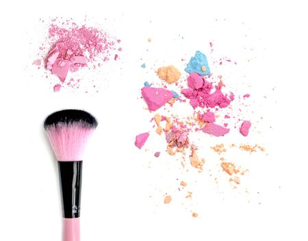 dispersed: Close up of crushed blush on white background and cosmetic brush