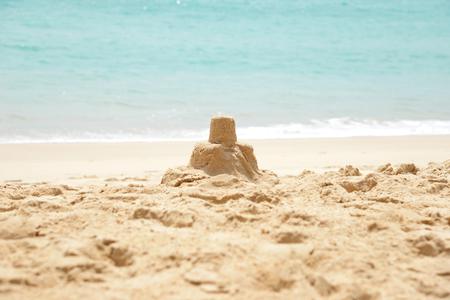 sandcastle: sandcastle on a sandy beach, set against a bright blue summer sky.