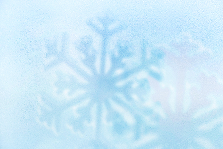Blue ice cold water drop with snowflake background. Winter holiday.
