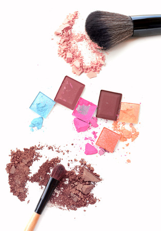 Close up of crushed blush on white background and cosmetic brush