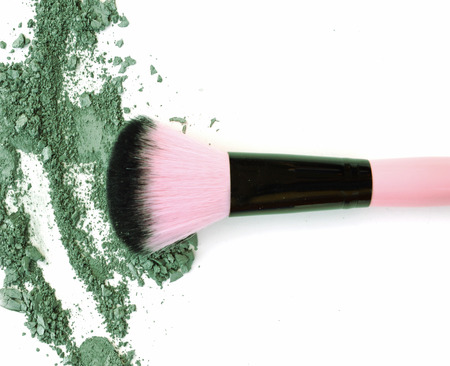 strewed: Makeup brush with green crushed eye shadow, isolated on white macro