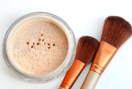 Close up of face powder and cosmetic brush