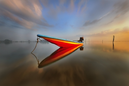 Colourful boat during sunrise with reflection photo