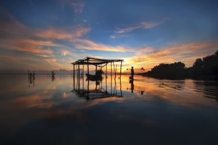 Beach with boat and hut during the fisherman start to work with beautiful sunrise photo