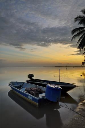 Beach with boat and beautiful sunrise photo