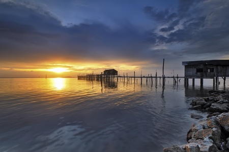 Fisherman floating house with golden cloudy sunset photo