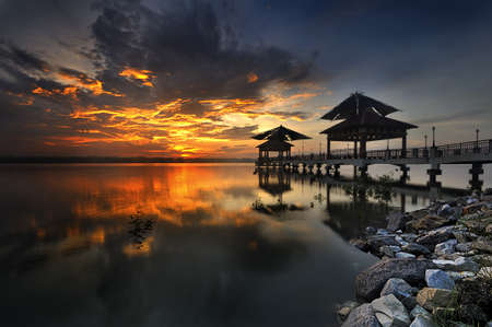 Golden Sunrise with rocks and fisherman jetty photo