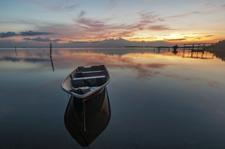 Sunrise scene with boats on the beach photo