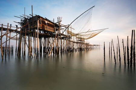 fishing hut: Traditional Fisherman hut with fishing net and wooden bridge on the sea with calm cloudy sky