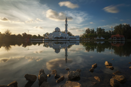 islamic wonderful: Holy white floating Mosque view during sunset scene with blue sky and reflection at a lake Stock Photo