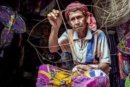 KOTA BHARU, MALAYSIA - FEBRUARY 19 : The master kite maker, Shafie Bin Jusoh works on his craft in a small hut near the Cahaya Bulan Beach, February 19, 2015 in Kota Bharu, Malaysia