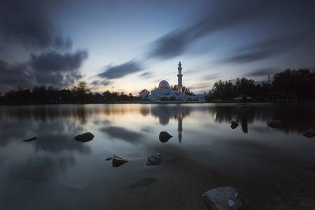 islamic wonderful: Runing clouds over Holy Mosque view during calm sunset with reflection at a lake Stock Photo