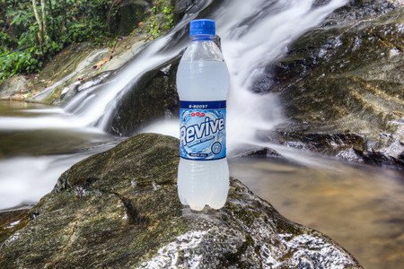 revive: SELANGOR, MALAYSIA - OCTOBER 25, 2015 : 7UP Revive looks fresh on the rocks with waterfall backgrounds.  7UP Revive has become one of the most popular drinks for young people with active lifestyles. Editorial