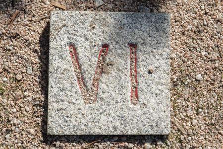 Roman numerals engraved on square granite stones