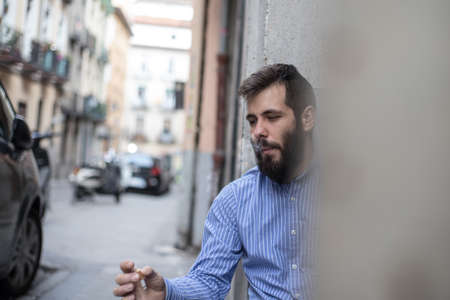 man with a beard sitting in a doorway and smoking