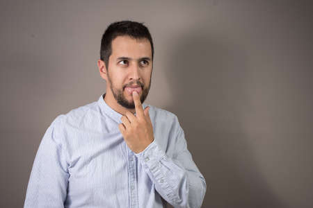 man thinking with his finger on his tongue