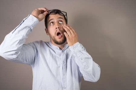 man throwing eye drops in his eyes