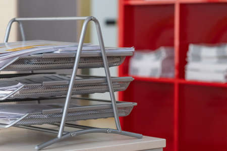 Office paper tray full of papers. Metallic tray of delivery notes. Stock Photo
