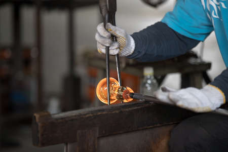 Molten glass on a metal rod for glass blowing
