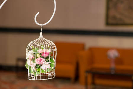 vintage wedding decorative birdcage with flowers on hotel background