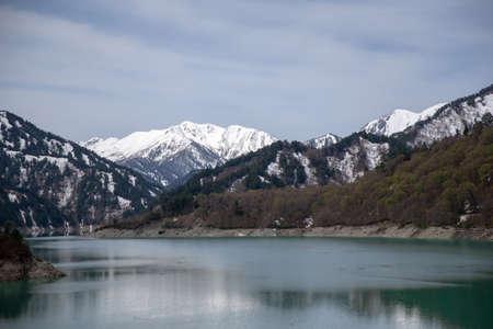 Scenery of lake and mountains from Kurobe Dam in spring at Tateyama Kurobe Alpine Route, Japan