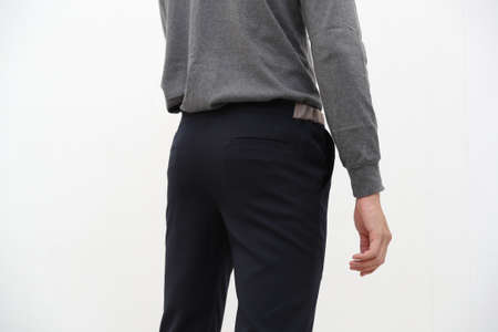 close-up of handsome man in gray turtleneck shirt and black long trousers on white background.