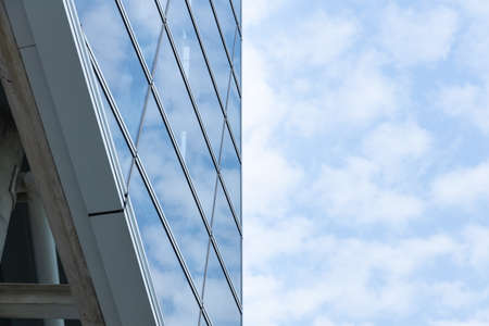 Cloud reflected on glass windows of building, Divided in half the building and the sky. 写真素材