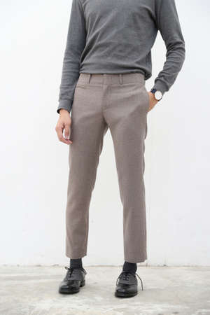 close-up of handsome man in gray turtleneck shirt and long trousers on white background.
