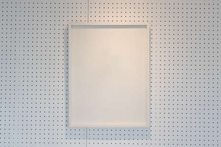 hanging empty wooden picture frame on orderly hole or dot wall with orange light form ceiling.