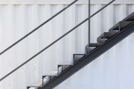 side view of outside metal staircase or fire exit stair with sheet corrugated wall background. Stock fotó
